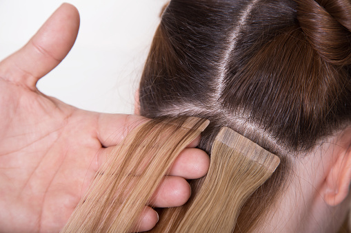 Natural Hair extensions at salon, close-up hands in hair. White background